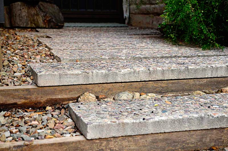 Exposed aggregate pavers are staggered to reflect the angles of the architecture, lead to the front door, and allow for edge plantings.